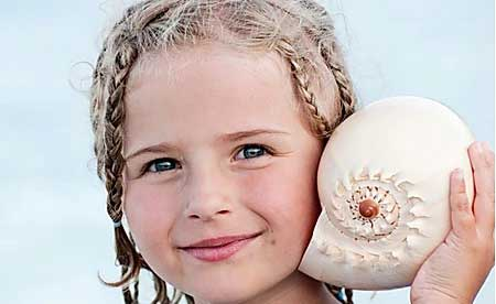 Small girl holding a shell
